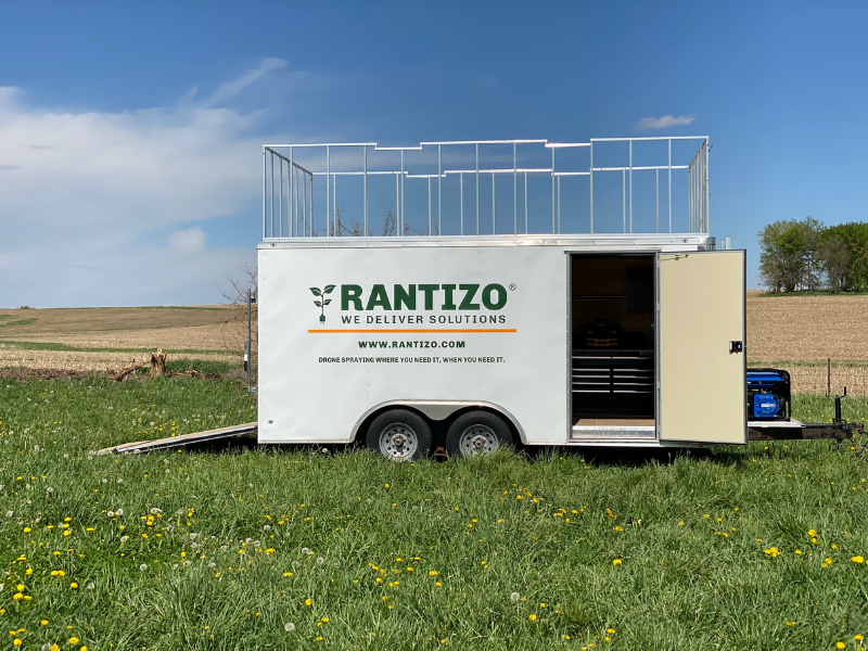 The Load & Go trailer as part of the Rantizo agricultural drone system is parked in a field and ready to go to work